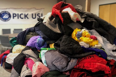 Coats and warm clothing stacked on a table that were donated from MBCU members